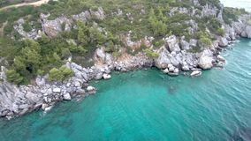 Aerial view of steep rocks in turquoise crystal sea in the area of Agia Paraskevi Halkidiki, Greece, circular movement by drone. Trees and rocks next to the stock video
