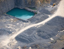 Aerial view : Stone quarry with a turquoise pond. And an excavator Stock Photography