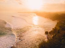Aerial view of stormy waves at warm sunrise and sandy beach. Biggest ocean wave in Bali stock image