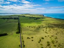 Aerial view of straight rural road passing through meadows and pastures on bright sunny day. Aerial view of straight rural road passing through meadows and Royalty Free Stock Image