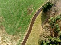 Aerial view of a stream flowing through meadows and fields with a small pine forest on one side stock photos