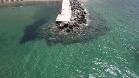 Aerial view of stunning turquoise sea in the summ. Crystal transparent sea with rocks that is round a jetty  in the area of Agia Paraskevi Halkidiki, Greece stock video footage