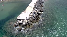 Aerial view of stunning turquoise sea in the summer with pier and rocks that water pops up on them in the area of Agia Paraskevi H. Crystal transparent sea with stock footage