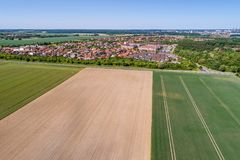 Aerial view of a suburb on the outskirts of Wolfsburg in Germany, with terraced houses, semi-detached houses and detached houses,. Arable land in the foreground Royalty Free Stock Photo