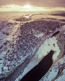 Aerial view of Suburban town next to a river and fields at sunset in winter. Royalty Free Stock Photo