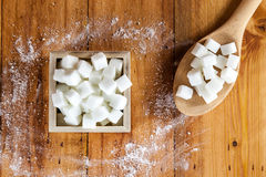 Aerial View of Sugar Cubes in Square Shaped Bowl and Spoon with Unrefined Sugar spill over in Wooden Background. Stock Photos