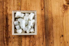 Aerial View of Sugar Cubes in Square Shaped Bowl with Unrefined Sugar spill over in Wooden Background Royalty Free Stock Photos