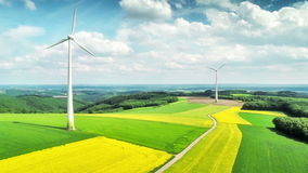 Aerial view of summer countryside with wind turbines and agricultural fields stock footage