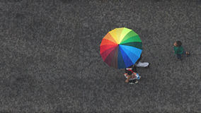 Aerial view of summer funny moment. People walking in rain with rainbow umbrella, a boy following Stock Photos