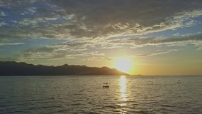 Aerial View Sun Rises from behind Hills on Horizon above Ocean. Aerial view sun rises from behind dark hills on horizon above boundless calm ocean against sky stock video footage