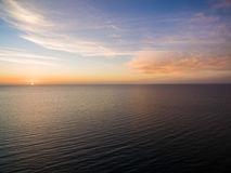 Aerial view of sun setting over ocean. Nothing but skies and wat. Er. Beautiful tranquil scene Royalty Free Stock Photo