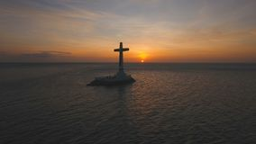 Catholic cross in the sea at sunset. Aerial view Sunken Cemetery cross at sunset in Camiguin Island, Philippines. Large crucafix marking the underwater sunken stock video footage