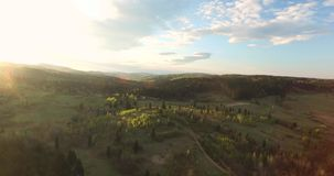 Aerial view. Sunny day over hilly terrain. Sunny day over hilly terrain, green hilly terrain over a long distance, grassy glade, blue sky with white clouds, few stock footage