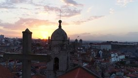 Drone flying above cathedral roof at sunrise. Aerial view sunrise in old european town with cloudy sky. Drone moving above roof of ancient cathedral with belfry stock video