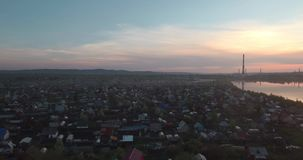 Aerial view. Sunset above the lake with small city on a shore. Industrial plant on a horizon. 4K. Aerial view. Sunset above the lake with small city on a shore stock footage