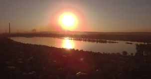 Aerial view. sunset above the lake with small city on a shore. Industrial plant on a horizon. 4K. Aerial view. sunset above the lake with small city on a shore stock video