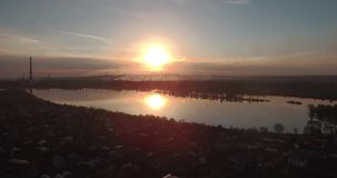 Aerial view. sunset above the lake with small city on a shore. Industrial plant on a horizon. 4K. Aerial view. sunset above the lake with small city on a shore stock video footage