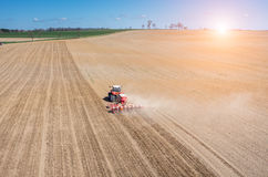 Aerial view of the sunset above the tractor harrowing the field Royalty Free Stock Photography