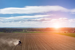 Aerial view of the sunset above the tractor harrowing the field Stock Photos