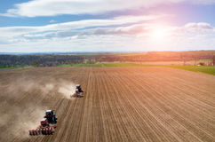 Aerial view of the sunset above the tractor harrowing the field Stock Image