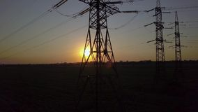 Sunset and High-voltage power pylon. Aerial View of Sunset and High-voltage power pylon. Fuel and power generation. 4K stock footage