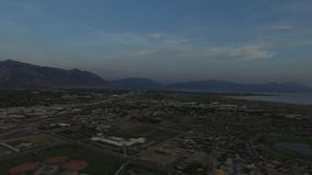 Aerial view of a sunset and panorama of an urban area with mountains in the background. Aerial view of a sunset on a large lake.  The water reflects on the water stock footage