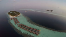 Aerial View sunset over the sea and luxurious overwater villas on tropical island resort, Maldives. Aerial View of sunset over the sea and luxurious overwater stock footage