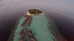 Aerial View sunset over the sea and luxurious overwater villas on tropical island resort, Maldives. stock footage