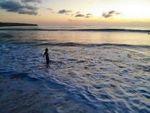 Aerial view of sunset over the sea with woman looking at the view, Bali, Indonesia. royalty free stock images