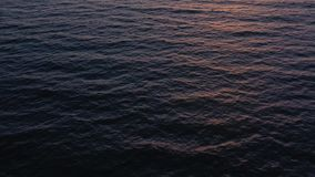 Aerial view of surface of the Atlantic Ocean with reflection of sunlight at sunset stock video
