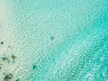 An aerial view of a surfer paddling at the beach with clear water royalty free stock image