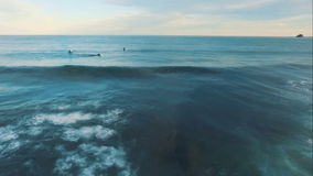 Aerial View. Surfers swim in the ocean at sunset. stock video footage