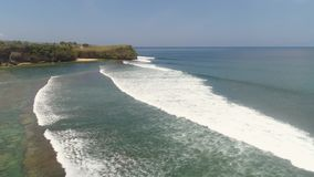 Surfers on the water surface. Aerial view surfers on water surface ocean catch wave. People learning to surf Bali, Indonesia stock footage