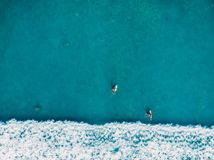 Aerial view of surfers and wave in tropical blue ocean. Top view Royalty Free Stock Image