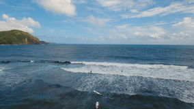 Aerial view surfers on the waves. Catanduanes, Philippines. Aerial view from drone of a swimming group with surfers in open sea with beautiful swell waves stock video footage