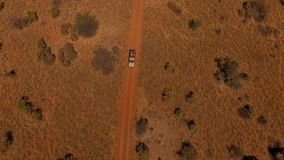 Aerial view: suv with people traveling on the road in the savannah of Namibia. The car goes off-road in Namibia`s savannah at sunset. Travelers go on an off stock video