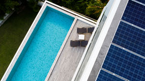Aerial view of swimming pool and solar panels. Top view of outdoor swimming pool and solar panels on the roof of villa Royalty Free Stock Image