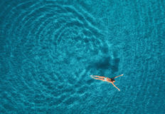 Aerial view of swimming woman in mediterranean sea. Aerial view of swimming woman in Blue Lagoon. Mediterranean sea in Oludeniz, Turkey. Summer seascape with Royalty Free Stock Images