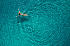 Aerial view of swimming woman in mediterranean sea. Aerial view of swimming woman in Blue Lagoon. Mediterranean sea in Oludeniz, Turkey. Summer seascape with stock photography