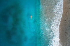 Aerial view of swimming woman in mediterranean sea. In Oludeniz, Turkey. Beautiful summer seascape with girl, clear azure water, waves and sandy beach in sunny Stock Images