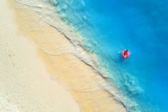Aerial view of a swimming woman in the sea at sunset royalty free stock photo