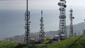 Aerial view of telecommunications towers antennas and cityscape in the background. Aerial view of one telecommunications tower with antennas and cityscape in the