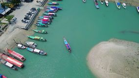 Aerial view of Thai traditional longtail boat approaching the wharf. Shot with DJI Mavic fps 29,97 4k stock footage