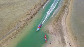 Aerial view of Thai traditional longtail boat sailing through waterway channel made in sand beach. Shot with DJI Mavic fps 29,97 4k stock footage