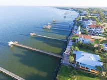 Kemah fishing piers aerial. Aerial view three-story waterfront vacation home with fishing piers stretching out over the Galveston Bay in Kemah city, Texas, USA Royalty Free Stock Photography