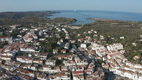 Drone view of beautiful seaside town Cadaques. Aerial view of tiled roofs, narrow streets, white houses of resort coastal town Cadaques on Cap de Creus peninsula stock video footage