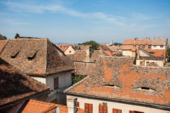 Aerial view of tiled rooftops. A house with attic windows like with smiling eyes Royalty Free Stock Images