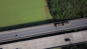 Aerial View of Timber Truck Driving across Bridge over Green Colored River. Cinematic Drone Shot Flying over Log Haulage stock video footage