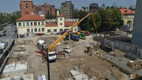 Aerial view of time lapse of a busy construction area, including laying foundations, manual workers, machinery, cranes