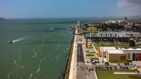 Belem tower and tourists at the riverside of Tejo River, timelapse. Aerial view timelapse of Belem tower and tourists at the riverside of Tejo River stock video